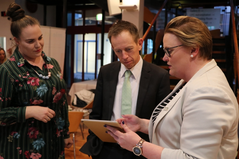 MIEACT program director Megan Mills (left) and executive officer Heidi Prowse (right) show Mental Health Minister Shane Rattenbury one of the interactive tools of the new bullying prevention program, No Labels.